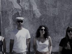 a girl-a guy-a girl-a girl. 4 people standing in front of a wall
